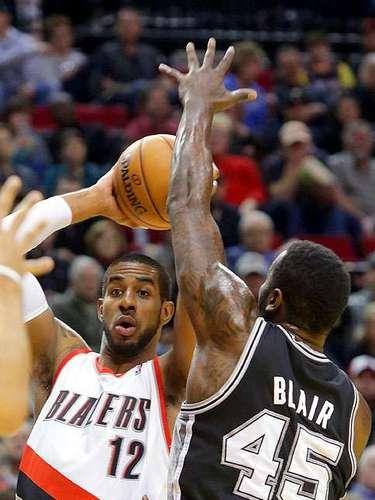 Spurs vs. Trail Blazers: LaMarcus Aldridge busca a un compañero para pasarle el balón ante la presión defensiva de DeJuan Blair.