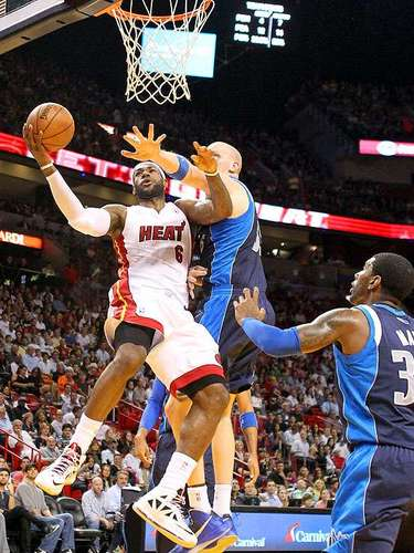 Mavericks vs. Heat:  LeBron James (6) intenta un disparo ante la marca de Chris Kaman y O.J. Mayo.