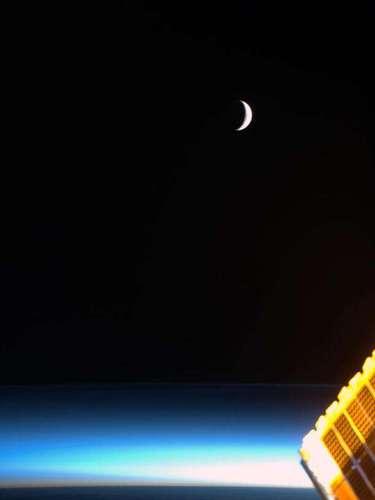Final de lanoche, la Luna al amanecer, con etéreas nubes noctilucentes azul y un oro brillante conjunto solar.