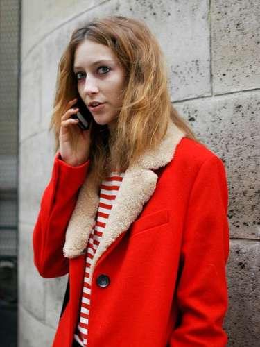 El rojo vivo del abrigo acompaña las rayas de la blusa, en un look casual con jeans.