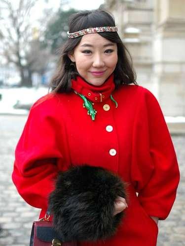 Las mangas voluminosas dan un toque de actualidad a este abrigo rojo pero destaca especialmente por el cocodrilo que lleva a manera de gargantilla.