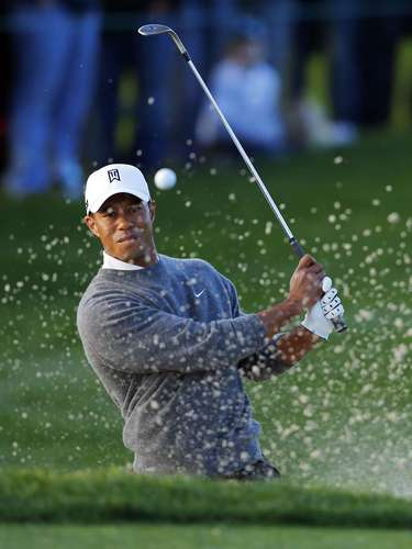 U.S. golfer Tiger Woods hits from a sand trap on the fifth hole during the weather-delayed fourth round play at the Farmers Insurance Open in San Diego, California January 27, 2013.