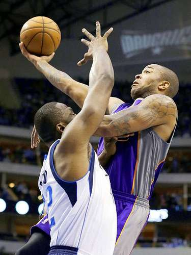 Suns vs. Mavericks: Elton Brand (42) intenta bloquear el paso de P.J. Tucker.