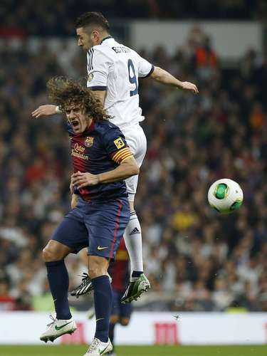 Karim Benzema (R) fights for the ball with Carles Puyol.