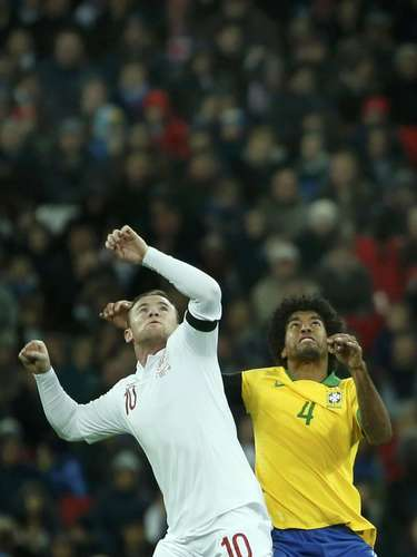 England's Wayne Rooney challenges Brazil's Dante (R) during their international friendly soccer match.