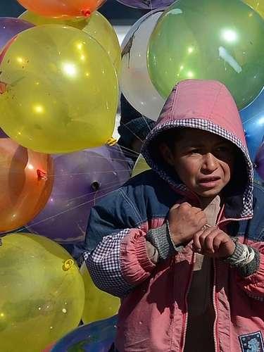 Un niño camina por las calles de Kabul en una fría mañana d einvierno para intentar vender sus globos de colores. A pesar de las inyecciones de dinero y ayuda internacional, Afganistán, sigue teniendo uno de los niveles de pobreza mayores del mundo