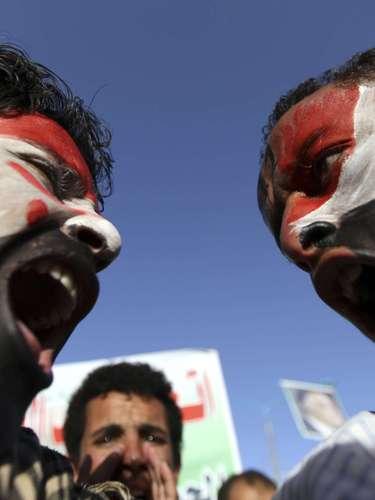 Dos manifestantes con la bandera de Yemen pintada en sus caras durante una manifestación para conmemorar los dos años de levantamiento en contra del ex presidente de Yemen