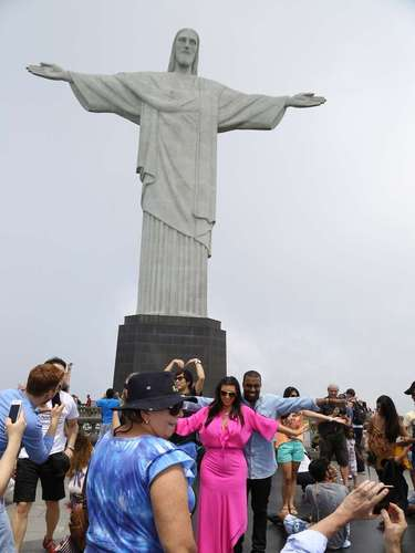 Con los brazos abiertos, pareja posa para la foto en frente del Cristo Redentor