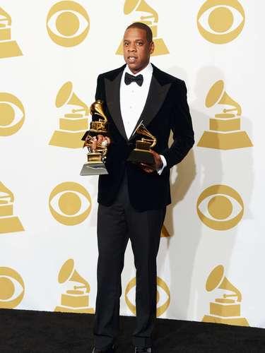 El cantante Jay-Z totalmente elegante celebra haberse llevado par de gramófonos a casa.