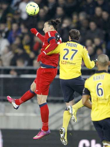 Sochaux's Loic Poujol (27) challenges Paris Saint Germain's Zlatan Ibrahimovic (L) during their French Ligue 1 soccer match at the Bonal stadium in Sochaux February 17, 2013.