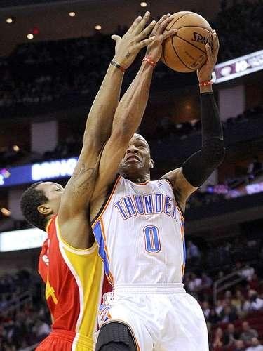 Thunder vs. Rockets:Russell Westbrook (0) intenta penetrar hasta la canasta ante la marca deGreg Smith (4)