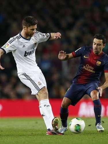 Xabi Alonso y Xavi pugnan por el balón.