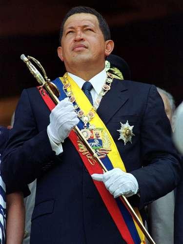 En esta fotografía de archivo del 24 de julio de 2000, se ve al presidente venezolano Hugo Chávez mientras sostiene la espada de Simón Bolívar en un evento para celebrar al héroe de la independencia en el 114to aniversario de su nacimiento en Caracas, Venezuela. El vicepresidente venezolano Nicolás Maduro anunció el martes 5 de marzo de 2013, que Chávez había muerto. (Foto AP/Andres Leighton, Archivo)