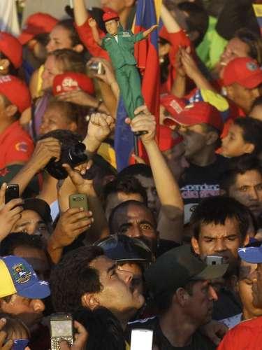 El vicepresidente venezolano Nicolás Maduro alza la cabeza, mientras se abre paso entre una muchedumbre de dolientes, durante el cortejo fúnebre del presidente Hugo Chávez en Caracas, el miércoles 6 de marzo de 2013. Arriba, un simpatizante de Chávez sostiene un muñeco con su imagen  (AP Photo/Fernando Llano)