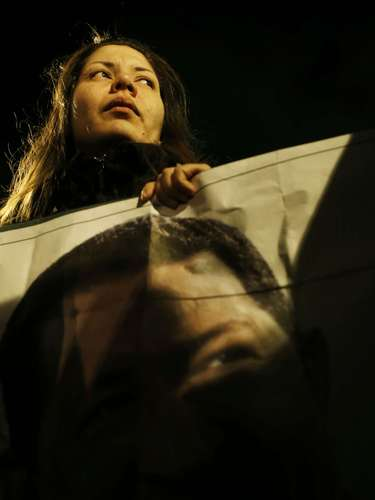 A woman holds a picture of the late Venezuelan President Hugo Chavez during a rally paying homage to him in Madrid March 6, 2013. Chavez died on Tuesday at age 58 after a two-year battle with cancer that was first detected in his pelvis. His body will be taken to a military academy on Wednesday to lie in state for three days before a state funeral. REUTERS/Susana Vera (SPAIN - Tags: POLITICS OBITUARY)