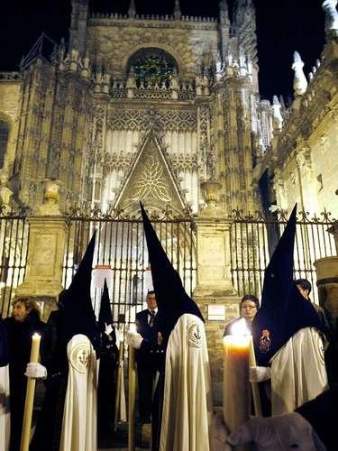 Nazarenos de la Hermandad de Triana pasan por la catedral de Sevilla durante su estación de penitencia en la madrugada del Viernes Santo.