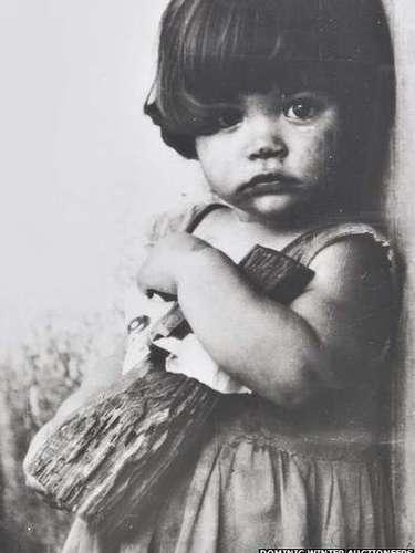 Otro tipo de fotografías no políticas también fueron incluidas en la subasta. Esta imagen de una niña con una muñeca de madera fue capturada en 1959 y era \