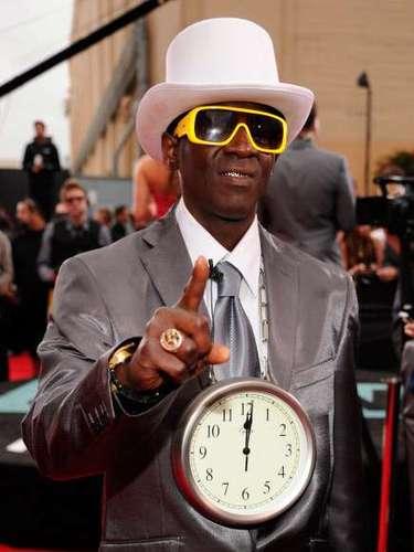 El atuendo y la actitud de Flavor Flav no es de extrañar.Suele lucir un reloj de agujas de un palmo de diámetro colgado del cuello, a juego con las gafas de sol y el tocado que lleve en cada ocasión. También acostumbra a llevar fundas de oro en los dientes, y se considera el iniciador de la moda de los dientes de oro o de platino en el mundo del hip hop. En cuanto a su vestimenta. Los relojes que lleva colgados en su cuello, no son simples relojes, son relojes de pared, algunos muy costosos, con partes de oro. ¡Definitivamente parece salido de un cuento infantil!