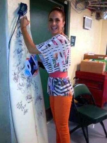 ¡Lucero pillada! La cantante posa para la foto autografiando la tabla de surf de esta cobertura de Premios Juventud
