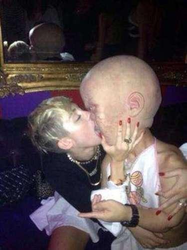 Miley Cyrus le estampó un beso a un hombre disfrazado de bebé gigante, pero no cualquier bebé. La máscara de su acompañante tenía un aspecto nada angelical. ¿Qué le estará pasando a la cantante estadounidense?