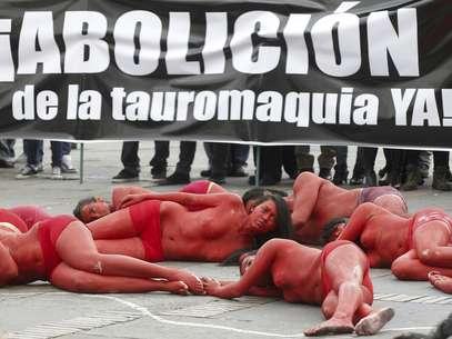 Jóvenes activistas yacen en el suelo con los cuerpos pintados de rojo simulando sangre en una protesta contra las corridas de toros en Bogotá, Colombia, el jueves 9 de febrero de 2012.  Foto: Fernando Vergara / AP