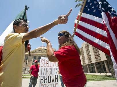 Andy Hernández, izquierda, y Allison Culver discuten sobre la ley SB1070 en el exterior del Capitolio del estado en Phoenix, Arizona, el lunes 25 de junio de 2012. Foto: AP
