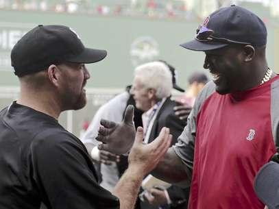 El tercera base de los Medias Blancas de Chicago Kevin Youkilis, izquierda, saluda a su ex compañero de equipo David Ortiz, bateador designado de los Medias Rojas de Boston, durante la práctica de bateo previa a su juego en el Fenway Park, el lunes 16 de juliuo de 2012, en Boston.  Foto: Charles Krupa / AP