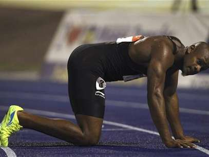 Asafa Powell kneels on the track after their men's 100 meters final event at the Jamaican Olympic trials in Kingston city, June 29, 2012. Foto: Ivan Alvarado / Reuters In English