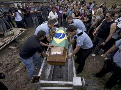 Varios policías colocan en la tumba el féretro con los restos de su compañero caído Diego Bruno Barbosa Henriques, en un cementerio en Río de Janeiro, Brasil, el viernes 14 de septiembre de 2012. Una bandera brasileña cubre el ataúd. Barbosa fue asesinado con arma de fuego el jueves en la noche mientras efectuaba un patrullaje a pie en el barrio pobre de Rocinha, en la ciudad. Barbosa es el tercer agente asesinado en los barrios pobres en los que las autoridades han reinstalado el orden en Río.  Foto: Víctor R. Caivano / AP
