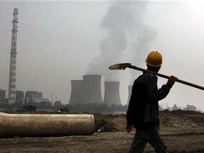 A coal-burning power station can be seen behind a migrant worker as he walks carrying his shovel on the construction site of a water canal, being built in a dried-up river bed located on the outskirts of Beijing October 22, 2010. Foto: David Gray / Reuters In English
