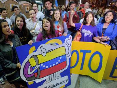 Ciudadanos venezolanos que residen en Estados Unidos cantan mientras aguardan fuera del Centro de Convenciones de Nueva Orleans Ernest Morial para sufragar en los comicios presidenciales de su país el domingo 7 de octubre de 2012. Foto: AP