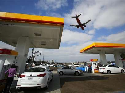 Consumers purchase gasoline at a gas station as a plane approaches to land at the airport in San Diego, California October 8, 2012. Foto: Mike Blake / Reuters