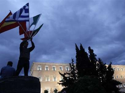 A protestor raises flags of Portugal, Italy, Greece and Spain in front of the parliament in Syntagma square during a 48-hour strike by the two major Greek workers unions in central Athens November 7, 2012. Foto: John Kolesidis / Reuters