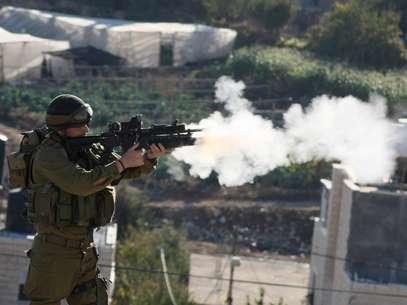 Un soldado israelí dispara gases lacrimógenos contra manifestantes palestinos en una ciudad de la Franja de Gaza. Foto: Getty Images