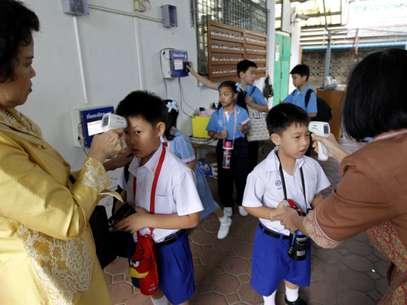 Profesoras tailandeses revisan la temperatura del cuerpo de sus estudiantes en busca de fiebre.  Foto: EFE