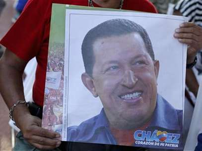 A supporter of Venezuelan President Hugo Chavez holds a picture of him, as he attends a mass to pray for Chavez's health in Caracas December 19, 2012. Foto: Carlos Garcia Rawlins / Reuters