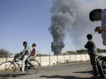 Onlookers stand as smoke billows from Indian Oil Corporation's fuel depot in Hazira, near Surat city of India's western state of Gujarat January 5, 2013. A major fire broke out at an IOC fuel depot on Saturday in Hazira with no reports of casualties or injuries, according to local media. Foto: Amit Dave / Reuters