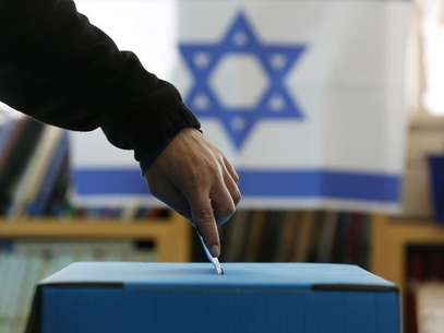 An Israeli flag is seen in the background as a man casts his ballot for the parliamentary election at a polling in the West Bank Jewish settlement of Ofra, north of Ramallah January 22, 2013. Foto: Baz Ratner / Reuters