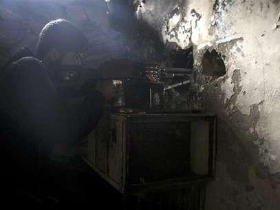 Un miembro del Ejército de Siria Libre apunta su arma a través de un agujero en una pared mientras toma una posición defensiva en Aleppo, feb 11 2013. Militantes opositores sirios capturaron un aeropuerto militar cercano a la ciudad de Alepo el martes, en otro revés para las fuerzas del presidente Bashar al-Assad, que han sufrido cada vez más ataques en todo el país. Foto: Aref Heretani / Reuters