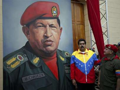 A supporter of Venezuelan President Hugo Chavez holds a copy of a photograph of Chavez released by the Ministry of Information, during a gathering at Plaza Bolivar in Caracas February 15, 2013. Foto: Carlos Garcia Rawlins / Reuters