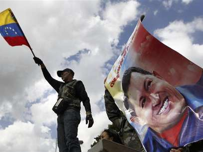 A supporter of Venezuela's President Hugo Chavez waves a national flag next to a giant picture of Chavez, in front of a military hospital where Chavez is being treated, in Caracas February 19, 2013. Foto: Carlos Garcia Rawlins / Reuters