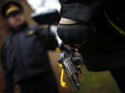 An Evanston police officer holds a firearm that was turned in as part of an amnesty-based gun buyback program in Evanston, Illinois December 15, 2012. Foto: Jim Young / Reuters
