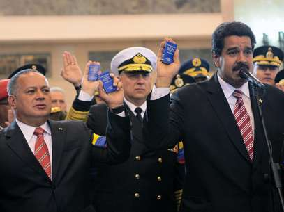 In this photo released by Miraflores Press Office, Venezuela's acting President Nicolas Maduro, right, the President of the National Assembly Disdado Cabello, left, and Defense Minister Adm. Diego Molero, center, hold up miniature copies of Venezuela's Constitution during a symbolic swearing in ceremony for Maduro in front of Venezuela's late President Hugo Chavez's coffin at the military academy where the funeral ceremony was held earlier, in Caracas, Venezuela, Friday, March 8, 2013. Chavez died on March 5 after a nearly two-year bout with cancer. Maduro was sworn in at the National Assembly earlier against the objections of the political opposition who said the move violated the country's constitution.   Foto: Miraflores Press Office / AP