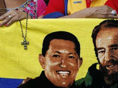 A supporter of Venezuela's President Hugo Chavez holds a crucifix next to a picture of Chavez with Cuba's former leader Fidel Castro (R) in Caracas January 5, 2013. Foto: Carlos Garcia Rawlins / Reuters