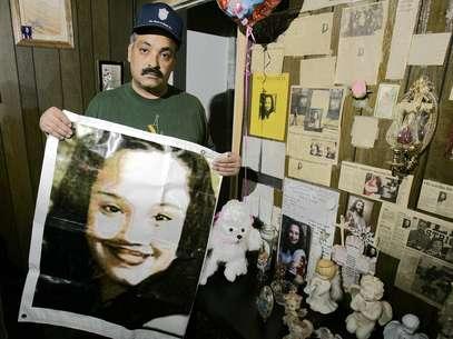 Felix DeJesus sostiene un afiche con la imagen de su hija desaparecida en una foto de archivo del 3 de marzo del 2004 frente a un altar de homenaje en la sala de su casa en Cleveland. Foto: AP