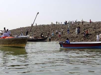 La curiosidad lleva a la gente a usar botes para llegar a la isla surgida tras terremoto dePakistán. Foto: STRINGER/PAKISTAN / REUTERS