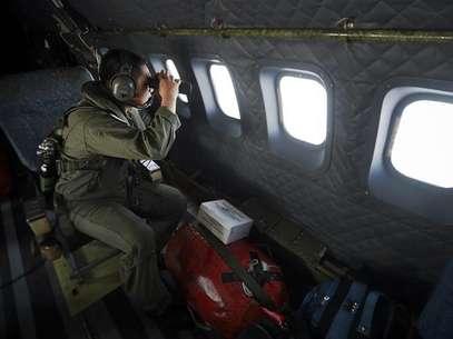 Un socorrista observa con binoculares durante la búsqueda del vuelo MH370 de Malaysia Airlines en el estrecho de Malacca, Indonesia, mar 14 2014. La investigación sobre la desaparición de un avión de Malaysia Airlines se centra cada vez más en la sospecha de que el vuelo fue desviado deliberadamente, ya que la evidencia sugiere que se dirigía hacia las islas Andamán fuera de su curso, dijeron fuentes familiares con la pesquisa. Foto: Junaidi Hanafiah / Reuters