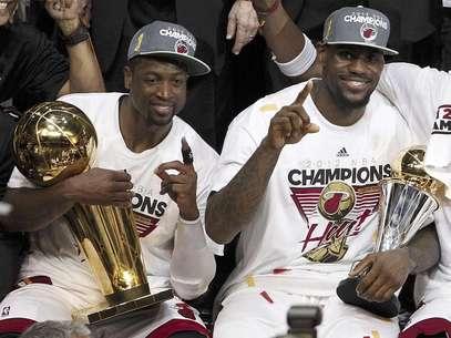 Dwyane Wade, del Heat de Miami, izquierda, posa con el Trofeo Larry O'Brien NBA del Campeonato de la NBA, mientras su compañero LeBron James sostiene su trofeo a Jugador Más Valioso, después de derrotar en la serie final de la liga al Thunder de Oklahoma, el jueves 21 de junio de 2012, en Miami.   Foto: Lynne Sladky / AP
