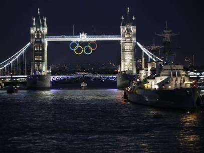 The Olympic rings are illuminated while suspended from Tower Bridge, near the HMS Belfast museum warship, as organisers marked one month to go until the London 2012 Olympic Games in London June 27, 2012. Foto: Chris Helgren / Reuters In English