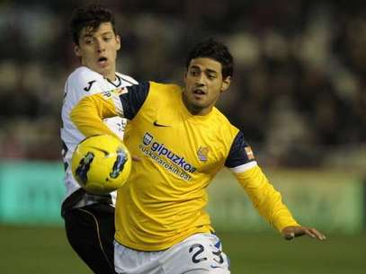 Valencia's defender Angel Dealbert (L) vies for the ball with Real Sociedad's Mexican forward Carlos Vela during the Spanish league football match Valencia CF vs Real Sociedad on January 14, 2012 at the Mestalla stadium in Valencia. Real Sociedad won 1-0. Foto: Getty Images